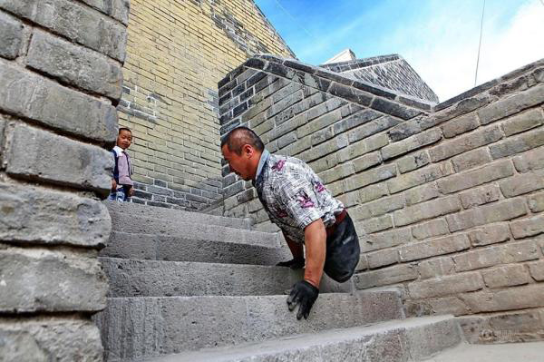 """Wang Xiaobing takes his son to climb the Zhangjiakou Dajingmen Great Wall on July 10. A netizen wrote on Weibo: """"I believe the image of him must be very tall in his sons heart! May this strong and persevering fathers family be happy and blessed!"""""""