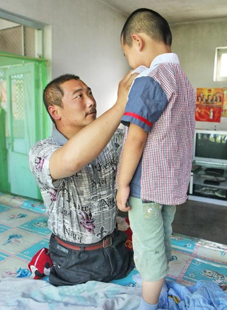 """Wang Xiaobing helps dress his child. He is a good father. A netizen wrote on Weibo: """"I believe the image of him must be very tall in his sons heart! May this strong and persevering fathers family be happy and blessed!"""""""