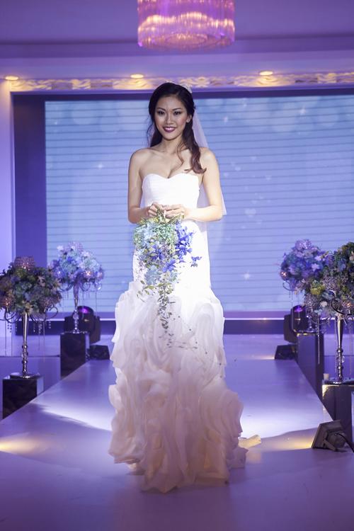 Đây là một trong những kiểu dáng hợp xu hướng cưới 2014 bởi kiểu dáng gọn nhẹ và phóng khoáng. Đặc biệt hơn, trên tay cô là bó hoa sắc tím xanh nhã nhặn, nổi bật khi kết hợp cùng bộ váy ren trắng.