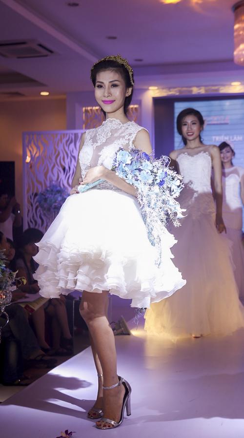 Lan Phương  người mẫu chuyển giới được biết đến qua cuộc thi Vietnams Next Top Model 2013 trông quyến rũ và năng động khi diện mẫu váy cưới ngắn hiện đại, trẻ trung. Mẫu váy có chất liệu voan ren, được xếp tầng sang trọng và tinh tế.