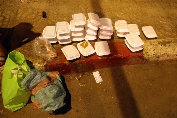 Những hộp cơm từ thiện và túi đồ của nạn nhân để lại hiện trường. Ảnh: Châu Thành