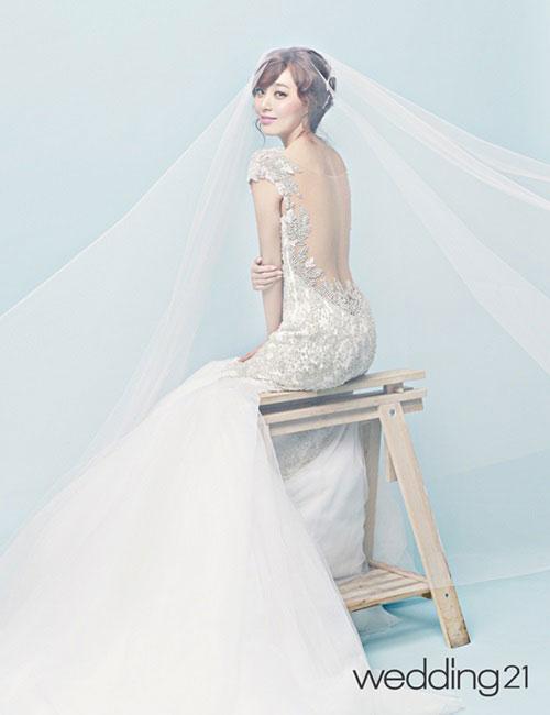 Thời trang cưới của các cô dâu Hàn luôn hướng đến sự thanh lịch, trang nhã. Chiếc váy đuôi cá khoe lưng trần gợi cảm, nhưng duyên dáng và kín đáo hơn khi cô dâu kết hợp với voan dài tha thướt. Ảnh: Kmib.