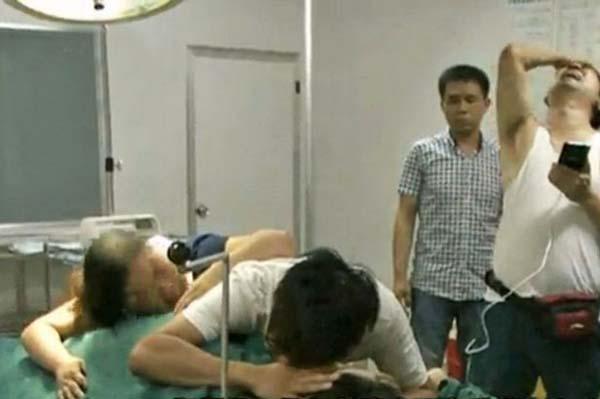 Người nhàđau khổ ôm xác cô Zhang Chun bị bỏ mặc chết trên bàn đẻ. Ảnh: Euripics