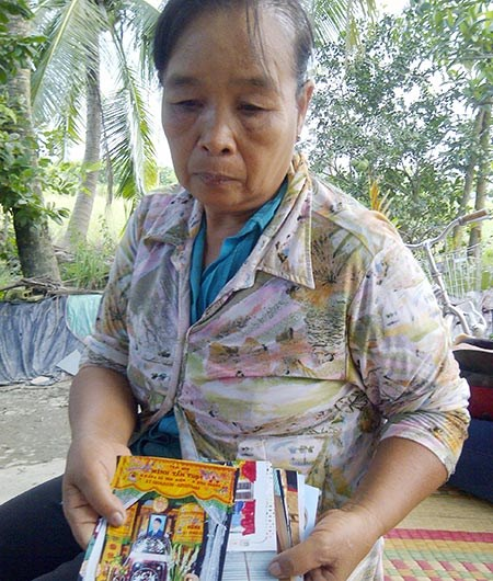 [Caption]Bà Xuyên cầm trên tay hình ảnh đám tang con trai bà.