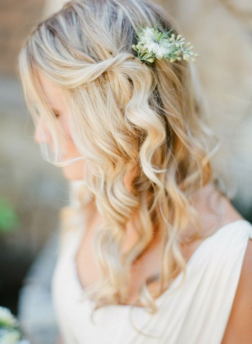 Mái tóc buộc nửa kết hợp hoàn hảo với hoa cài đầu. Cô dâu nên uốn lọn xoăn nhẹ nhàng để mái tóc ghi điểm với phong cách bồng bềnh, lãng mạn.