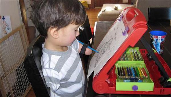 Không có tay chân, cậu bé tự học làm mọi việc bằng miệng. Trong ảnh cậu bé dùng miệng để vẽ tranh.