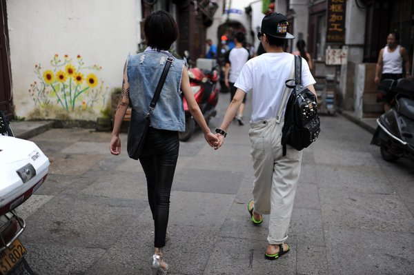 Lin Daqi wears a new outfit Zhou Xiaomai bought for her, as the couple walks in Zhoushan city, East China's Zhejiang province on Aug 9. Lin and Zhou were born in 1980s and they live in the city.