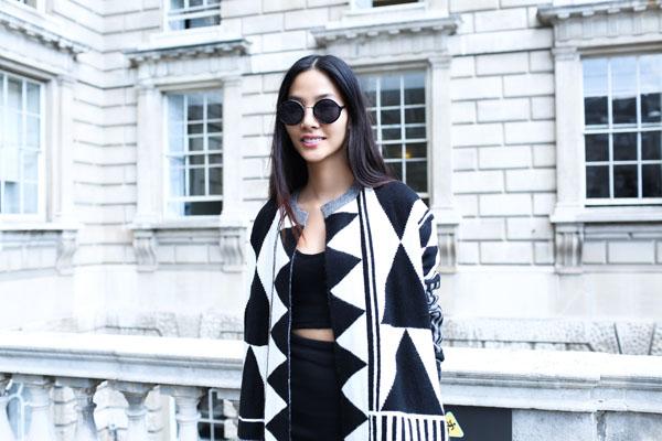 Hoàng Thùy chọn cho mình chiếc áo khoác dài theo phong cách op art nổi bật của mùa Thu - Đông 2014 với những hoạ tiết hình học  bắt mắt. Kết hợp cùng nó là chiếc váy bút chì và áo crop top sành điệu.