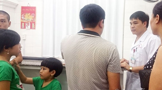 [Caption]Bác sĩ thăm khám cho 3 bố con anh Dương tại bệnh viện.