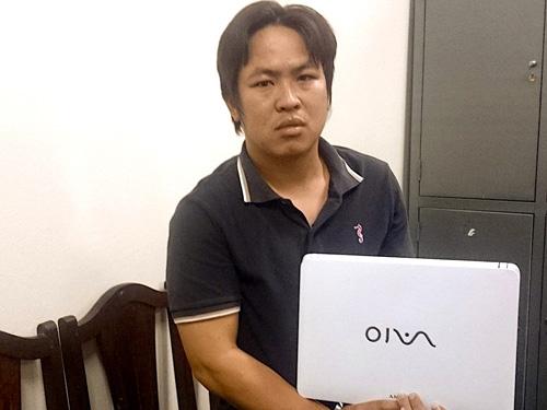 Nguyễn Đình Phòng sau khi bị bắt giữ tại cơ quan công an cùng tang vật là chiếc máy tính hiệu Vaio