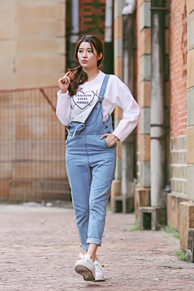 Street style tinh nghịch của cô nàng 9X này với quần jeans yếm, áo pull tay dài kết hợp với giày thể thao khỏe khoắn.