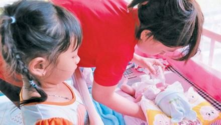 Cháu Huy trong vòng tay dì và chị gái.