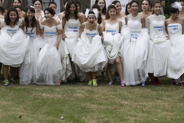 Brides-to-be get ready for the Running of the Brides race in a park in Bangkok November 29, 2014. Seventy-five husbands and wives-to-be wore their wedding dresses and running shoes and competed in an event for a combined prize worth 1 million Thai baht ($30,460).