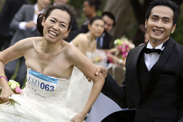 A man and his fiancee run to victory during the Running of the Brides race in a park in Bangkok November 29, 2014