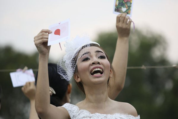 A woman gestures to her fiance during the Running of the Brides race in a park in Bangkok November 29, 2014.