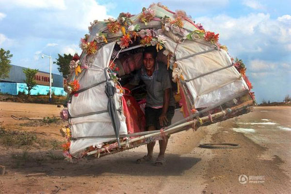 "39 year old Liu Lingchao from Liuzhou city of Guangxi Autonomous Region, has spent six years collecting discarded waste and bottles for a living and making annual trips with his collected paraphernalia on his back to his hometown, garnering him the nickname of ""Snail Man""."