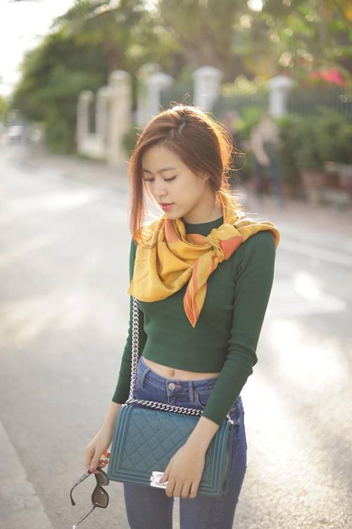 Áo dệt kim hở eo phối nhẹ nhàng cùng jeans xanh cổ điển và Hoàng Thùy Linh thêm điểm nhấn ấm áp cho mình bằng mẫu khăn choàng gam màu cỏ úa đầy lãng mạn.