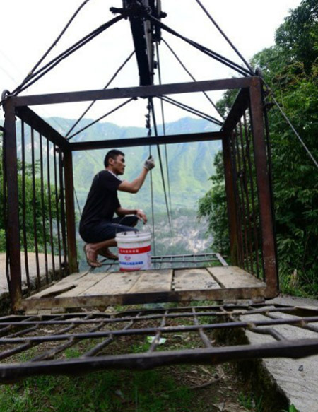 A cableway operator named Zhang Xinjian is photographed oiling the cable.