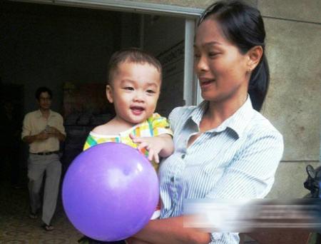 [Caption]Cháu bé bị bỏ rơi vẫn đang hạnh phúc trong vòng tay chăm sóc của các nữ cán bộ phường 1, quận 8, TP.HCM