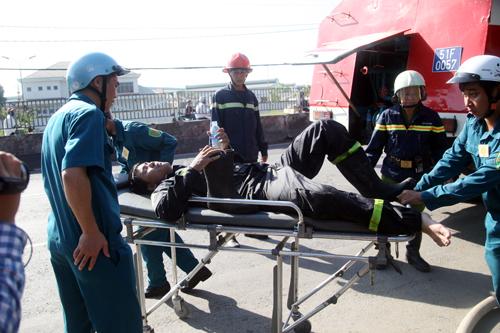 Một cảnh sát cứu hỏa bị thương phải lên băng ca đưa xe xe cứu thương.