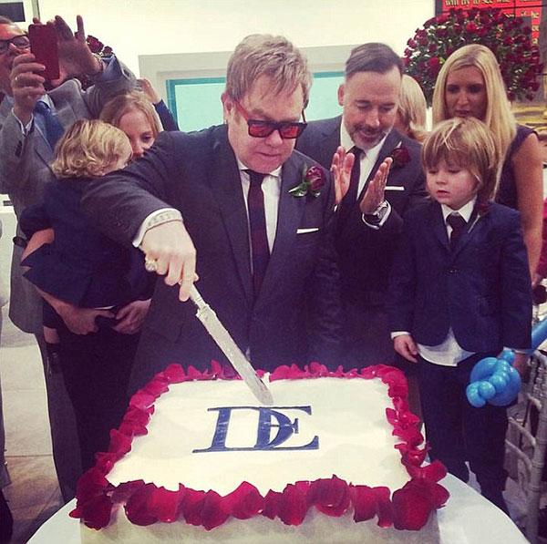Bánh cưới đính cánh hoa hồng xung quanh, nổi bật bên trên là hai chữ cái lồng vào nhau, tên của David và Elton.