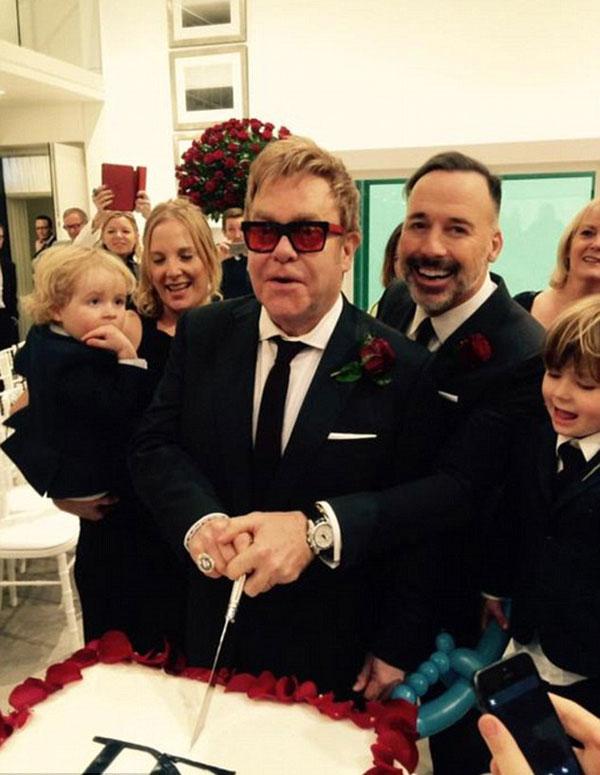 """""""Vợ chồng"""" Elton John rạng rỡ cắt bánh cưới. Bên cạnh họ là hai cậu con trai kháu khỉnh Zachary 4 tuổi và Elijah 2 tuổi."""