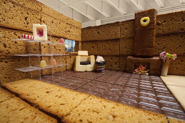 Sàn phòng khách bằng chocolate, trang trí kệ sách, ghế và cả lò sưởi ấm cúng.