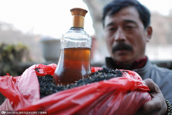 Chen shows fried ants and a bottle of medicinal liquor soaked with silky ants at his home in his village