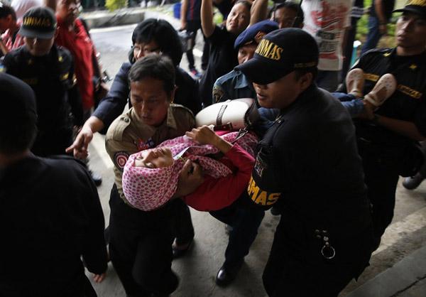 Lực lượng an ninh ở sân bay Juanda, Indonesia đưa một phụ nữ bị ngất vào phòng cấp cứu. Ảnh: Reuters