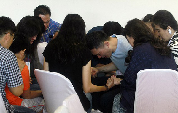 Relatives of passengers of ill-fated AirAsia flight QZ8501 pray together as they wait for the latest news on the missing jet at Juanda International Airport in Surabaya