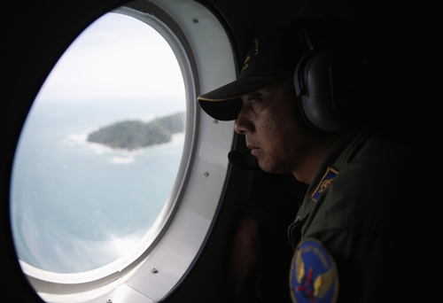 A crew member on an Indonesian Maritime Surveillance looks out the window during a search for AirAsia's Flight QZ8501, north of Bangka island December 30, 2014. Indonesian rescuers saw bodies and luggage off the coast of Borneo island on Tuesday and officials said they were