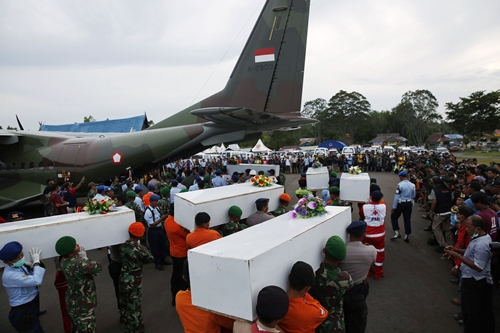 Caskets containing the remains of AirAsia QZ8501 passengers recovered from the sea are carried to a military transport plane before being transported to Surabaya, where the flight originated, at the airport in Pangkalan Bun, Central Kalimantan January 2, 2015. Ships and aircraft criss-crossed the seas off Borneo on Friday hunting for the wreck of the Indonesia AirAsia passenger jet, but bad weather was again hindering the search for the plane and the black box flight recorders that should reveal why it crashed. REUTERS/Darren Whiteside (INDONESIA - Tags: TRANSPORT MILITARY DISASTER TPX IMAGES OF THE DAY)
