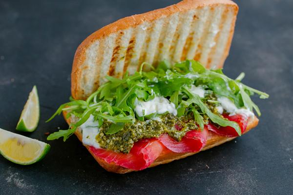 Bánh mì kẹp cá hồi muối củ dền, sốt pesto ớt chuông và rau xà lách romaine.