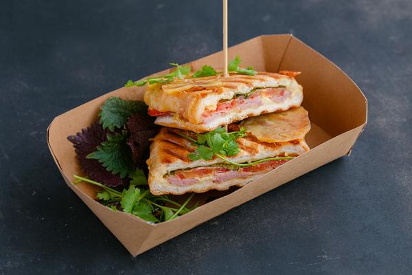 Bánh mì Panini thịt nguội, phô mai, cà chua với sốt mù tạt và rau chân vịt.
