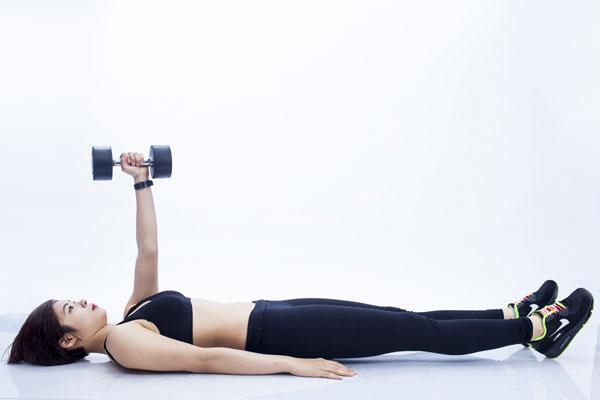 Bắt đầu với tư thế nằm trên sàn, một tay nâng tạ theo hưởng thẳng 90 độ