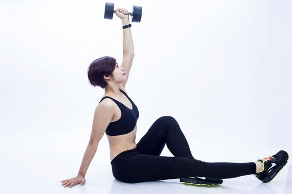 Dùng cơ bụng nâng gập người vuông góc 90 độ đồng thời chân cùng bên tay tạ co lên trong khi tay vẫn giữ tạ thẳng như tư thế ban đầu