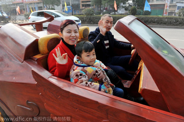 Yu drives his homemade wooden sports car with his family on a road in Guangfeng county.