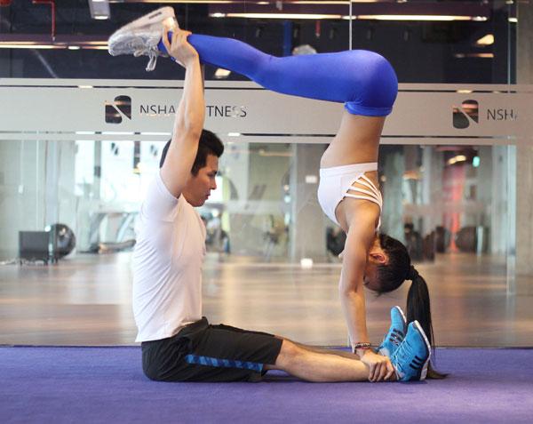 Nam giữ nguyên tay hướng lên trần, từ từ gập bụng ngồi dậy, đồng thời nữ siết bụng, kéo hông lên cao đến khi nào cả 2 ở vị trí vuông góc. Sau đó từ từ trở về tư thế ban đầu. (lên thở ra, xuống hít vào)
