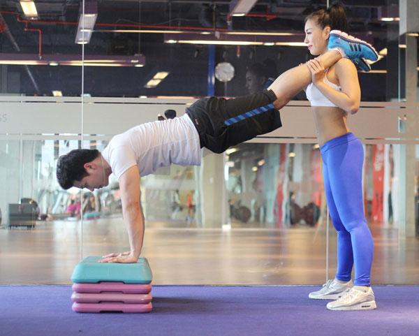 Nam tư thế chống sấp 2 tay trên bục tập, có thể thay thế bằng bậc thang. Đưa 1 chân lên cho nữ băt lên vai trước sau đó đưa chân còn lại.