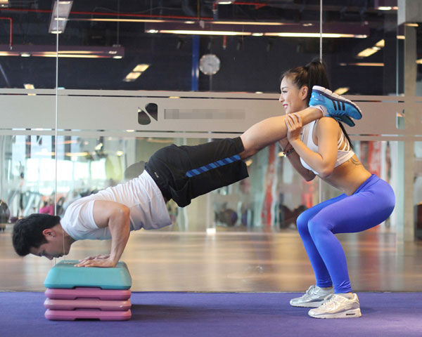 Đồng thời trong cùng 1 lúc: siết bụng, nam chống đẩy, nữ xuống tư thế squats. Lưu ý giữ đúng kỹ thuật chống đẩy và squat khi thực hiện: nam giữ lưng thẳng, nữ đẩy hông về sau.
