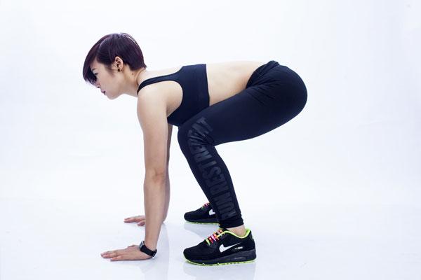 Trùng gối, đẩy mông ra sau và hạ thấp phần mông xuống, đồng thời đưa thân trên và vai xuống. - 2 tay chạm đất, chú ý cánh tay thẳng, đặt bàn tay sát mũi chân