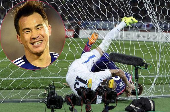 Shinji Okazaki che chắn để bóng tự lăn vào lưới trong nỗ lực truy cản của hậu vệ Uzbekistan. Ảnh: AP.