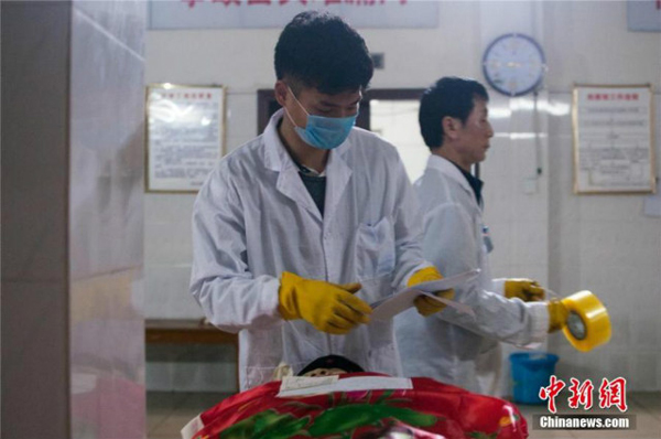 Liu checks the identity of one of the deceased.