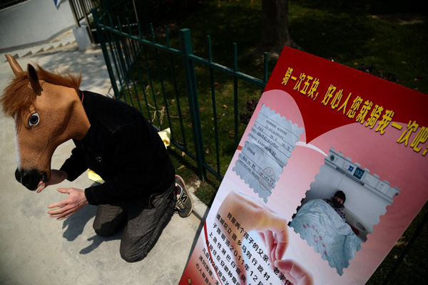 Chen Yuntao, wearing a horse head mask, kneels beside a billboard advertising 5 yuan ($0.8) rides on his back on a road in Hefei, capital city of East China's Anhui province April 13, 2015. Chen is trying to raise money to help his 9-year-old son, Chen Minghao, who has leukemia, because his family cannot afford the medical fees, which cost at least 400,000 yuan ($64,440)  a huge sum of money for an ordinary family. Many passers-by donated some money to help the poor father without taking up his offer of a ride on his back.[