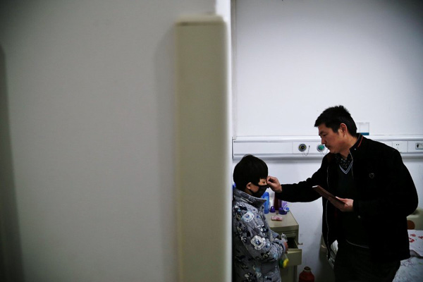 Chen Yuntao helps his son wear a mask at the hospital's ward so as to prevent infection, because a local citizen wants to see his son on Monday.