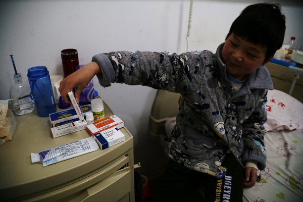 Chen Minghao, the 9-year-old with leukemia, says he is not afraid of taking the medicines on the desk at the hospital's ward in Hefei, capital city of East China's Anhui province on Monday. He says he wants to beat the leukemia and go back to study with his classmates.