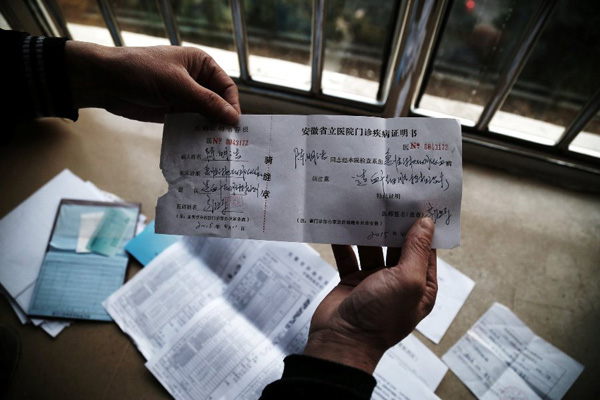 Chen Yuntao shows the diagnosis issued by Anhui Provincial Hospital on Monday. Chen says that he will use this certificate to apply for severe illness aid in his hometown.