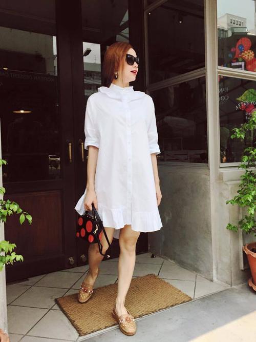 """Váy sơ mi trắng với thiết kế """"thùng thình"""" mang lại cảm giác thoải mái được Minh Hằng chọn lựa sử dụng trong những ngày nắng đầu mùa."""