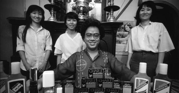 [Caption] Một tấm ảnh của phóng viên Philip Jones Griffiths chụp ông Nguyễn Văn Mười Hai năm 1988, không lâu trước khi vào vòng lao lý. Khi đó, ông là lãnh đạo của nhà máy nước hoa Thanh Hương, đang cùng các nhân viên hào hứng khoe thành quả của mình.