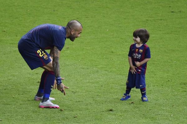Milan bạo dạn chạy trên sân, cười nắc nẻ khi một đồng đội của bố trêu đùa.